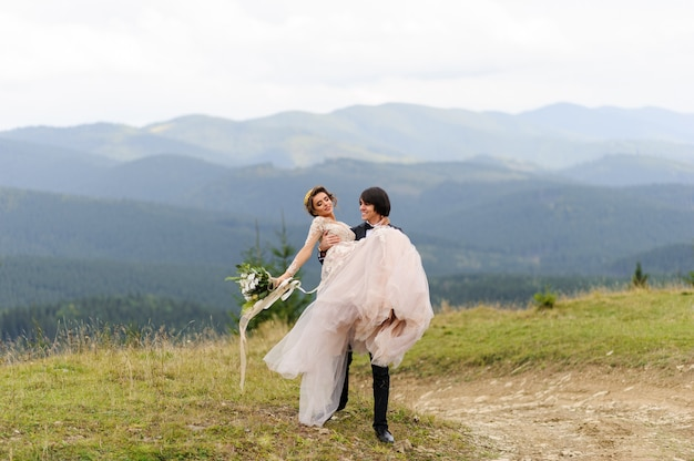 Lo sposo porta la sua sposa tra le sue braccia. fotografia di matrimonio in montagna.