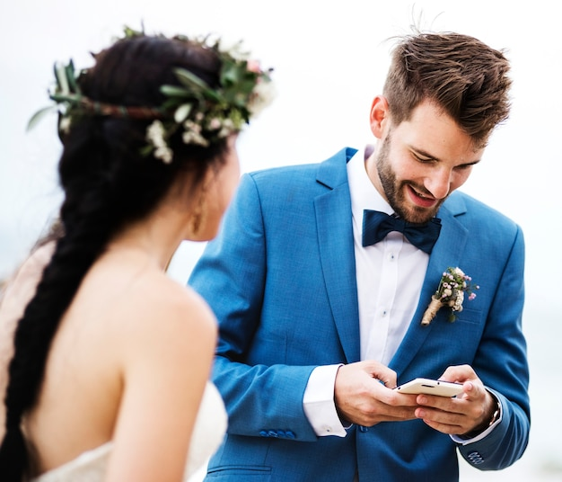 Sposo che controlla il suo telefono alla cerimonia di nozze della spiaggia