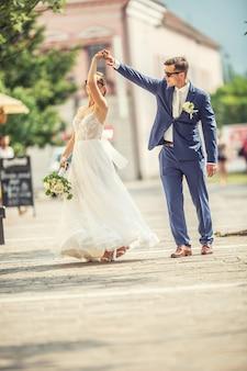 Uno sposo che balla con la sposa in città dopo un matrimonio. indossa ancora splendidi abiti e tiene in mano un mazzo di fiori bianchi.,