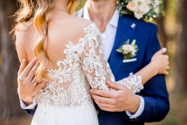 Lo sposo abbraccia la sposa. foto dal retro. bellissimo vestito con pizzo.