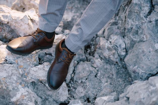 Piedi dello sposo in scarpe su un primo piano della roccia