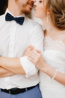 Lo sposo incrocia le braccia sul petto, la sposa lo abbraccia dolcemente per il gomito e sta per baciarlo