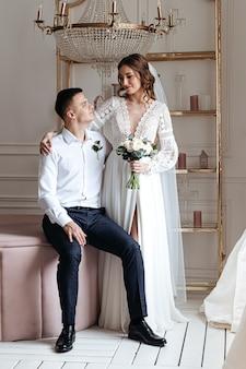 Lo sposo abbraccia dolcemente la sposa in un bellissimo abito di pizzo con un bouquet di fiori freschi.
