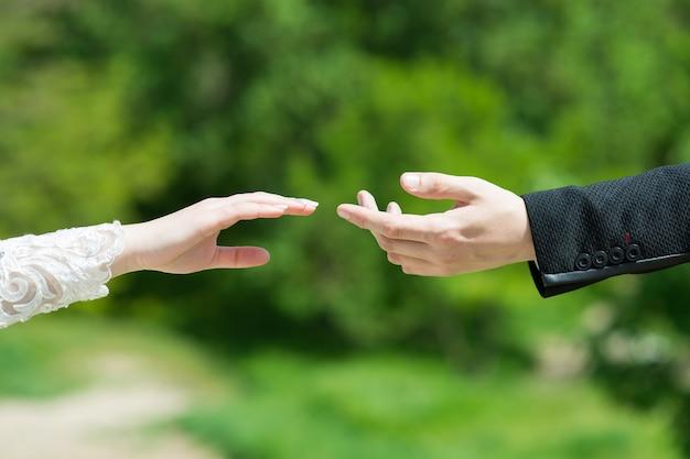 Lo sposo tocca delicatamente le dita della sposa con il suo primo piano della mano
