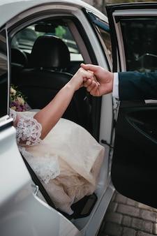 Lo sposo dà le mani alla sposa fuori dall'auto per matrimoni