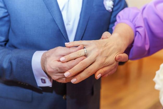 Mano dello sposo che mette anello nuziale sul dito della sposa