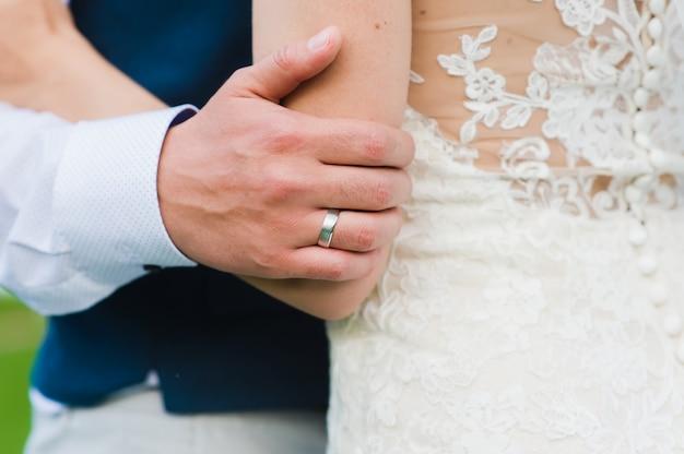 Mano dello sposo con anello di fidanzamento