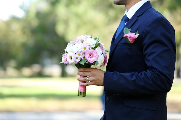 Sposo che tiene il mazzo di nozze all'aperto