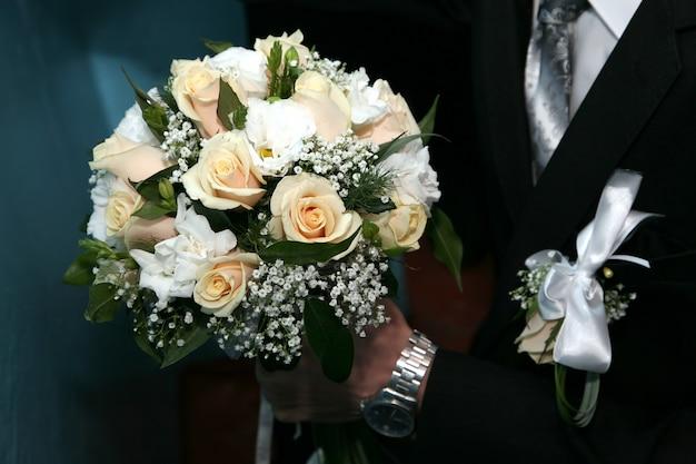 Sposo che tiene il mazzo di nozze delle rose