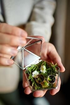 Sposo che tiene le fedi nuziali all'interno della scatola rustica fatta a mano decorativa con le piante