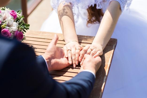 Lo sposo tiene le mani della sposa mentre è seduto al tavolo