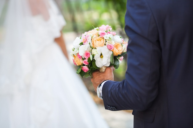 Lo sposo detiene il bouquet da sposa di fiori