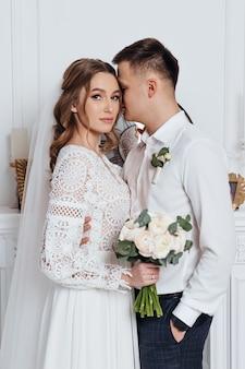 Lo sposo abbraccia la sposa in un abito da sposa in pizzo stile boho in una stanza accogliente.