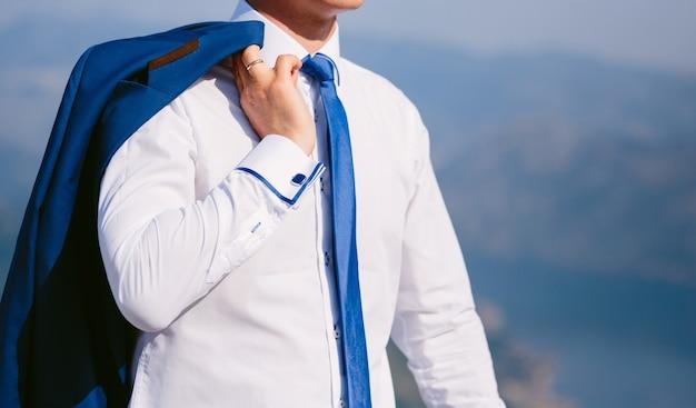 Lo sposo tiene la giacca sulle spalle