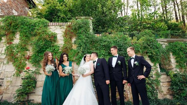 Lo sposo bacia le damigelle della sposa e i testimoni dello sposo vicino agli sposini