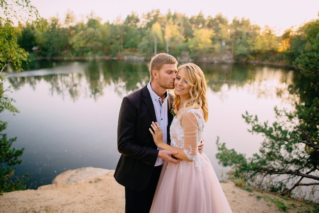 Lo sposo bacia una sposa felice sullo sfondo della natura al tramonto