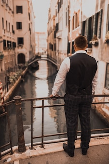 Lo sposo guarda il canale di venezia