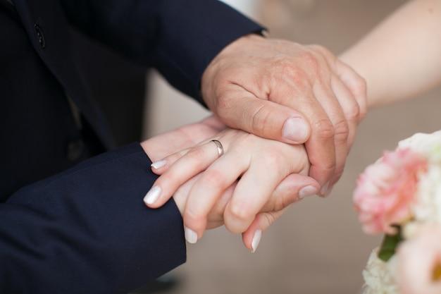 Lo sposo ha messo la mano sul palmo della sposa con l'anello d'oro al dito. coppia di sposini mostra i loro anelli di nozze.