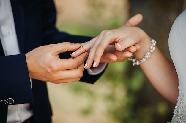 Lo sposo mette un anello di fidanzamento al dito della sposa il giorno delle nozze.