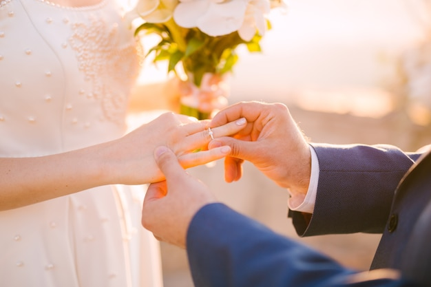 Lo sposo mette l'anello al dito della sposa durante la cerimonia nuziale.