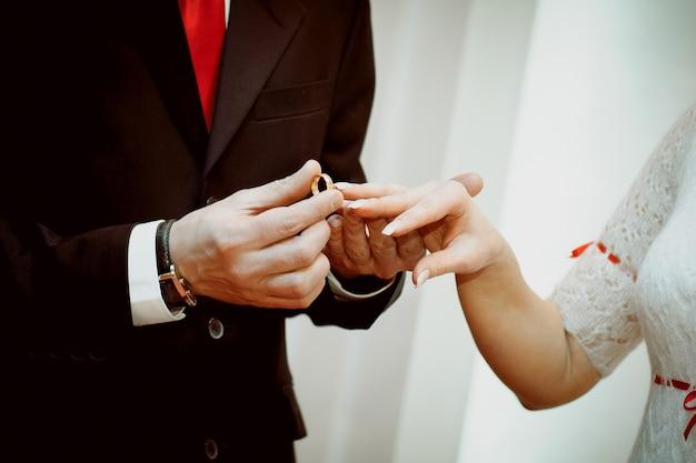 Lo sposo mette l'anello sulla mano della sposa. mani degli sposi il giorno del matrimonio