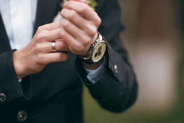 Uno sposo che indossa i gemelli mentre si veste in abiti formali. un uomo raddrizza i gemelli. abito da sposo