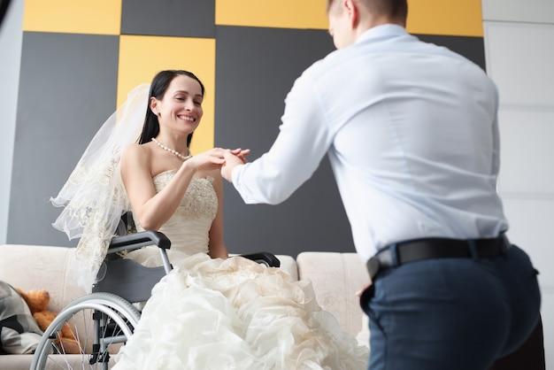 Sposo che mette l'anello al dito della sposa in sedia a rotelle. vita piena del concetto di persone disabili