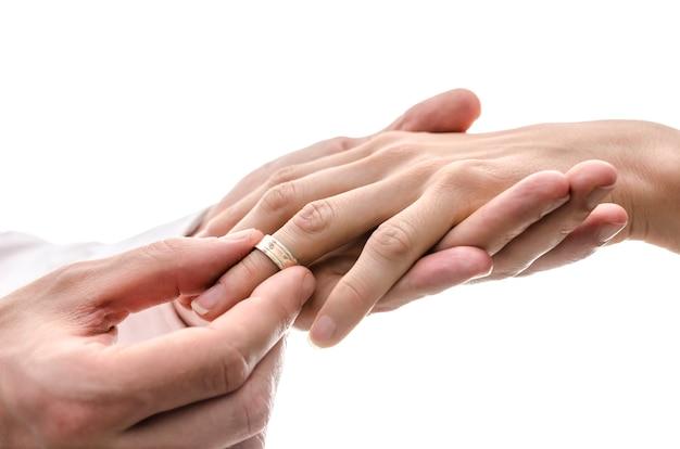 Sposo che mette un anello nuziale al dito della sposa. isolato su uno spazio bianco.