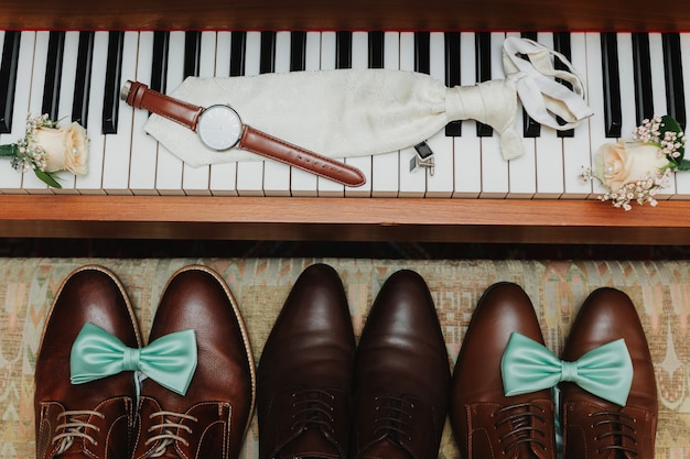 Accessori da sposo. orologio elegante, cravatta, boutonniere e gemelli sui tasti per pianoforte. le scarpe dello sposo con la cravatta blu su di loro stanno vicino al piano. mattina dello sposo.
