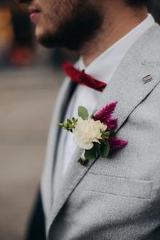 Il boutonniere bordeaux dello sposo. lo sposo in una giacca.