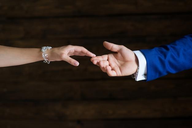 La mano dello sposo tocca il primo piano della mano della sposa