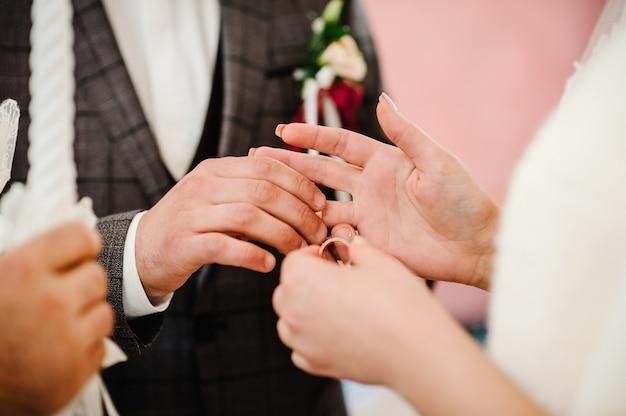 La mano dello sposo indossa un anello d'oro di fidanzamento al dito della sposa. giorno del matrimonio. mani con fedi nuziali. avvicinamento.