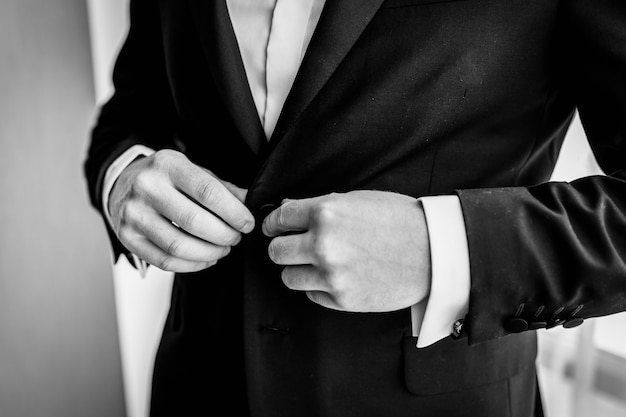 I preparativi dello sposo per il matrimonio. lo sposo abbottona la giacca. nozze foto in bianco e nero concetto. avvicinamento.