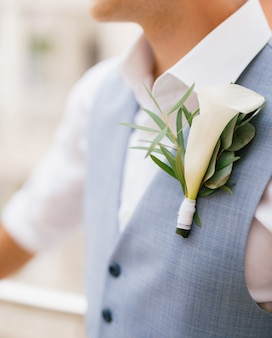 Lo sposo in camicia e gilet con un fiore all'occhiello si trova sul balcone la mattina prima del