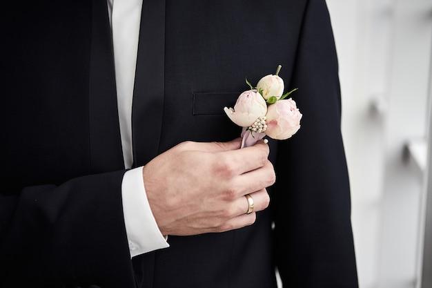 Lo sposo raddrizza il fiore nella tasca esterna della giacca