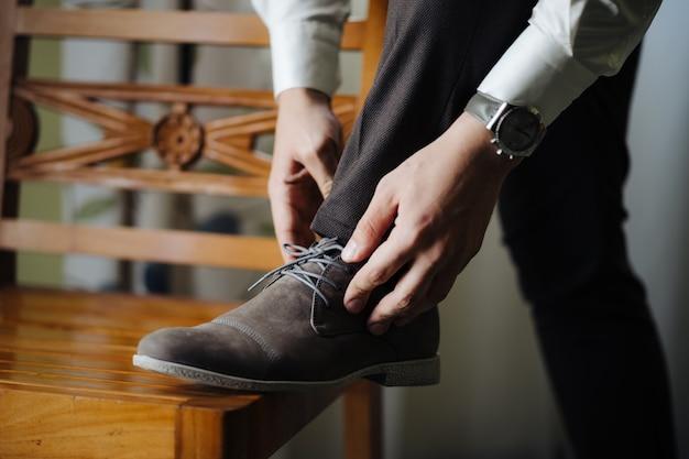 Lo sposo raddrizza i lacci allacciati con il piede sulla sedia