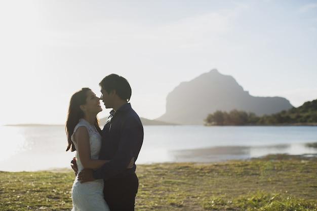 Sposo in abito e la sposa in abito bianco in piedi sulla riva di un lago di montagna