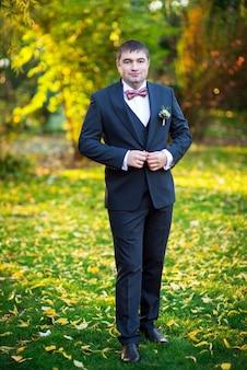 Lo sposo in abito abbottona i bottoni