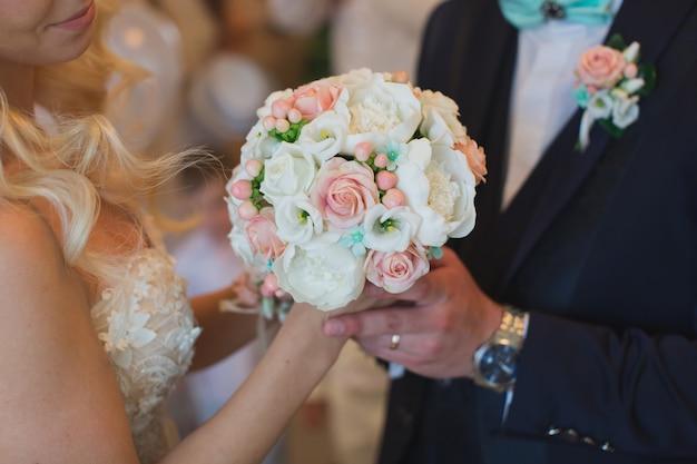 Lo sposo in abito regala alla sposa un bouquet da sposa bianco e pesca