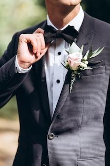 Lo sposo in abito raddrizza la cravatta bubochku. boutonniere sul risvolto della giacca. giovane uomo in giacca e cravatta.