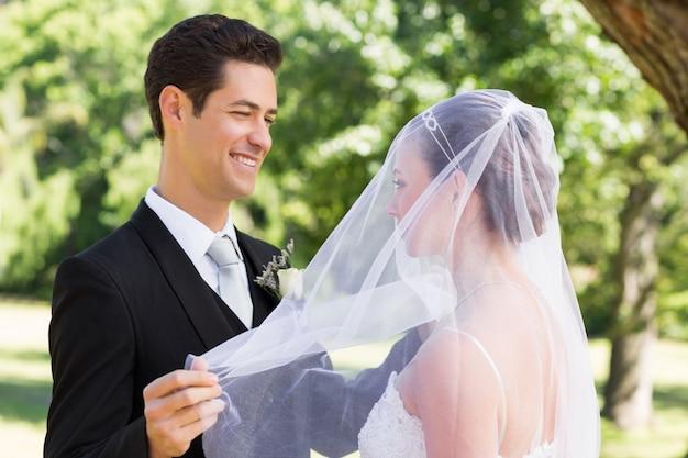 Sposo che rivela la sua sposa in giardino