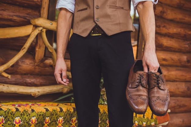 Uno sposo e scarpe da sposa. lo sposo indossa scarpe all'aperto. ritratto maschile di bel ragazzo.