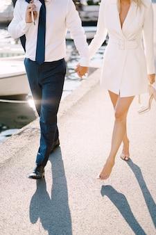 Lo sposo con la sposa a piedi nudi cammina tenendosi per mano lungo il molo sullo sfondo degli yacht