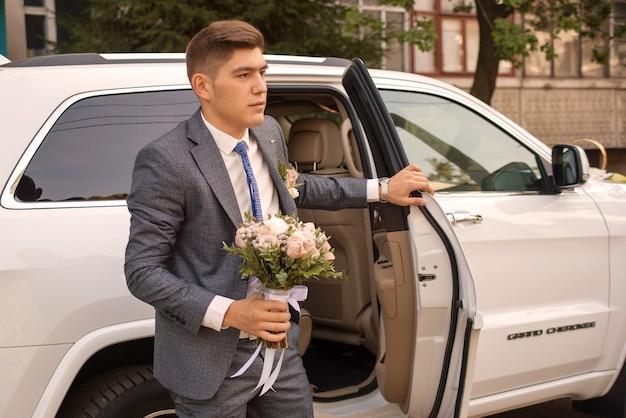 Sposo con bouquet il giorno del matrimonio