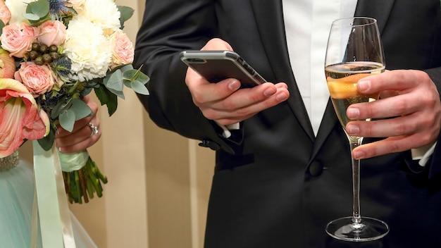 Lo sposo con cellulare e bicchiere in mano. moderni mezzi di comunicazione tra le persone