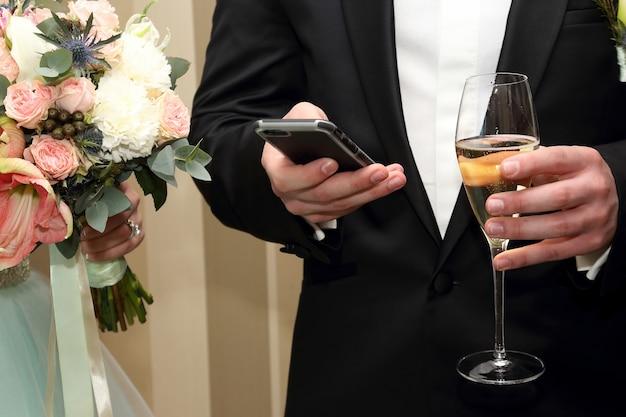 Lo sposo con cellulare e bicchiere in mano
