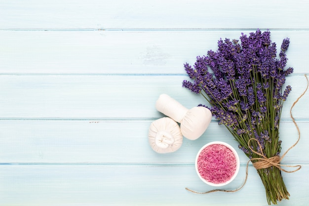 Prodotti per la toelettatura e bouquet di lavanda fresca sul fondo della tavola in legno bianco.