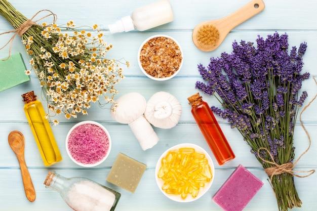 Prodotti per la toelettatura e bouquet di lavanda fresca sulla tavola di legno bianco.