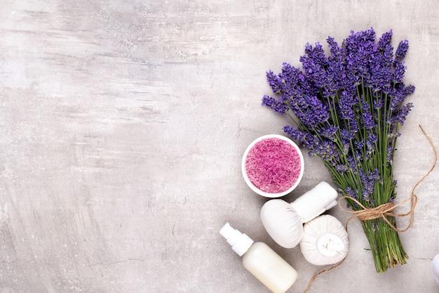 Prodotti per toelettatura e bouquet di lavanda fresca sulla tavola di legno bianco.