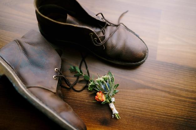 Il bocciolo dello sposo e le scarpe da uomo in pelle marrone sono su una trama di legno